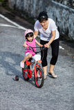 Asian Chinese little girl riding bicycle with mom guide Stock Photo