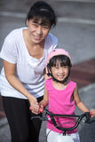 Asian Chinese little girl riding bicycle with mom guide Royalty Free Stock Photos