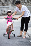 Asian Chinese little girl riding bicycle with mom guide Royalty Free Stock Image