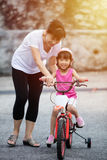 Asian Chinese little girl riding bicycle with mom guide Stock Image