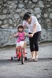 Asian Chinese little girl riding bicycle with mom guide Royalty Free Stock Images