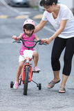 Asian Chinese little girl riding bicycle with mom guide Stock Photos