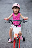 Asian Chinese little girl riding bicycle on tar road Stock Images