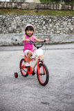 Asian Chinese little girl riding bicycle on tar road Stock Image