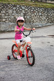Asian Chinese little girl riding bicycle on tar road Stock Photo