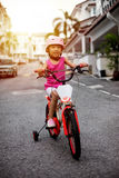 Asian Chinese little girl riding bicycle on tar road Royalty Free Stock Images