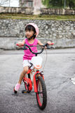 Asian Chinese little girl riding bicycle on tar road Stock Photography