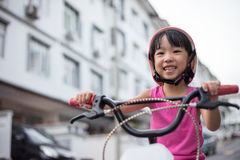 Asian Chinese little girl riding bicycle on tar road Stock Photos