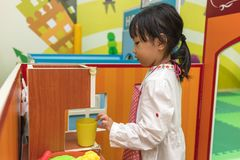 Asian Chinese little girl role-playing at burger store. At indoor playground Stock Images