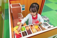 Asian Chinese little girl role-playing at burger store. At indoor playground Royalty Free Stock Photo