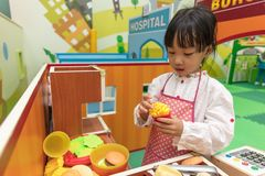 Asian Chinese little girl role-playing at burger store. At indoor playground Royalty Free Stock Photos
