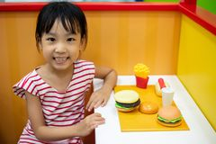 Asian Chinese little girl role-playing at burger store stock images
