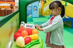 Asian Chinese little girl role-playing at fruits store. At indoor playground Royalty Free Stock Photo
