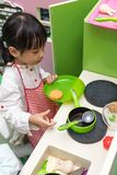 Asian Chinese little girl role-playing at kitchen Royalty Free Stock Images