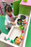Asian Chinese little girl role-playing at kitchen. At indoor playground Royalty Free Stock Image