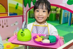 Asian Chinese little girl role-playing at kitchen. At indoor playground Stock Photography