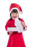 Asian Chinese little girl in santa costume holding gift box Royalty Free Stock Images