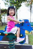 Asian Chinese little girl on seesaw at playground Royalty Free Stock Photos