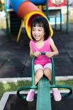 Asian Chinese little girl on seesaw at playground Royalty Free Stock Photography