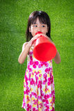 Asian Chinese little girl shouting through megaphone. At outdoor park Stock Photography