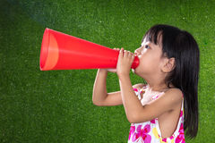Asian Chinese little girl shouting through megaphone. At outdoor park Stock Photos