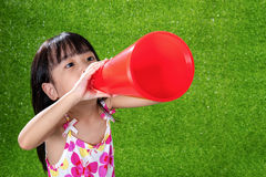 Asian Chinese little girl shouting through megaphone. At outdoor park Stock Images