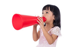 Asian Chinese little girl shouting with retro loudspeaker. In isolated white background Royalty Free Stock Photo