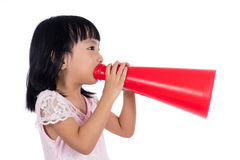 Asian Chinese little girl shouting with retro loudspeaker. In isolated white background Royalty Free Stock Image