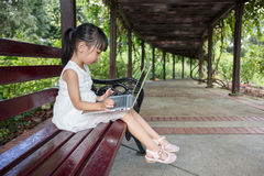 Asian Chinese little girl sitting on the bench with laptop. In outdoor garden Stock Photos