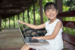 Asian Chinese little girl sitting on the bench with laptop. In outdoor garden Royalty Free Stock Photos