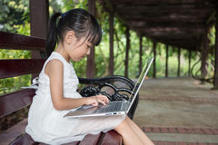 Asian Chinese little girl sitting on the bench with laptop. In outdoor garden Stock Photo