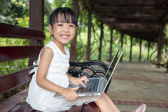 Asian Chinese little girl sitting on the bench with laptop. In outdoor garden Stock Image