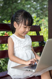 Asian Chinese little girl sitting on the bench with laptop. In outdoor garden Stock Images