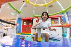 Asian Chinese little girl sitting in the carousel stock image