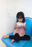 Asian Chinese little girl sitting inside a MRT with phone royalty free stock photography