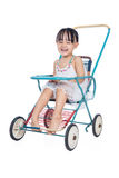 Asian Chinese little girl sitting in a retro stroller Royalty Free Stock Images