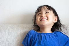 Asian Chinese little girl sitting on the sofa. In the living room at home Stock Image