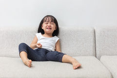 Asian Chinese little girl sitting on the sofa crying Stock Photography