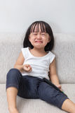 Asian Chinese little girl sitting on the sofa crying Stock Images