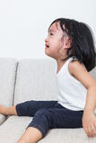 Asian Chinese little girl sitting on the sofa crying Stock Photos