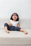 Asian Chinese little girl sitting on the sofa crying Royalty Free Stock Photography