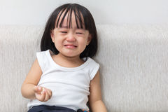 Asian Chinese little girl sitting on the sofa crying Royalty Free Stock Images
