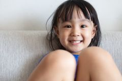 Asian Chinese little girl sitting on the sofa. In the living room at home Royalty Free Stock Photography