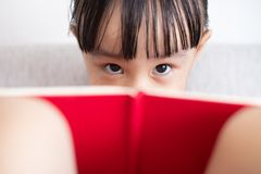 Asian Chinese little girl sitting on the sofa reading book. In the living room at home Royalty Free Stock Images