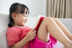 Asian Chinese little girl sitting on the sofa reading book. In the living room at home Royalty Free Stock Photography