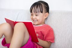 Asian Chinese little girl sitting on the sofa reading book. In the living room at home Stock Image