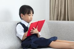Asian Chinese little girl sitting on the sofa reading book. In the living room at home Stock Images