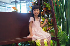 Asian Chinese little girl sitting on a swing Stock Photo
