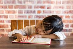 Asian chinese little girl sleeping on table while doing homework Royalty Free Stock Photos