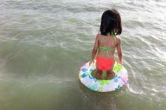 Asian Chinese little girl stepping into sea water Royalty Free Stock Image